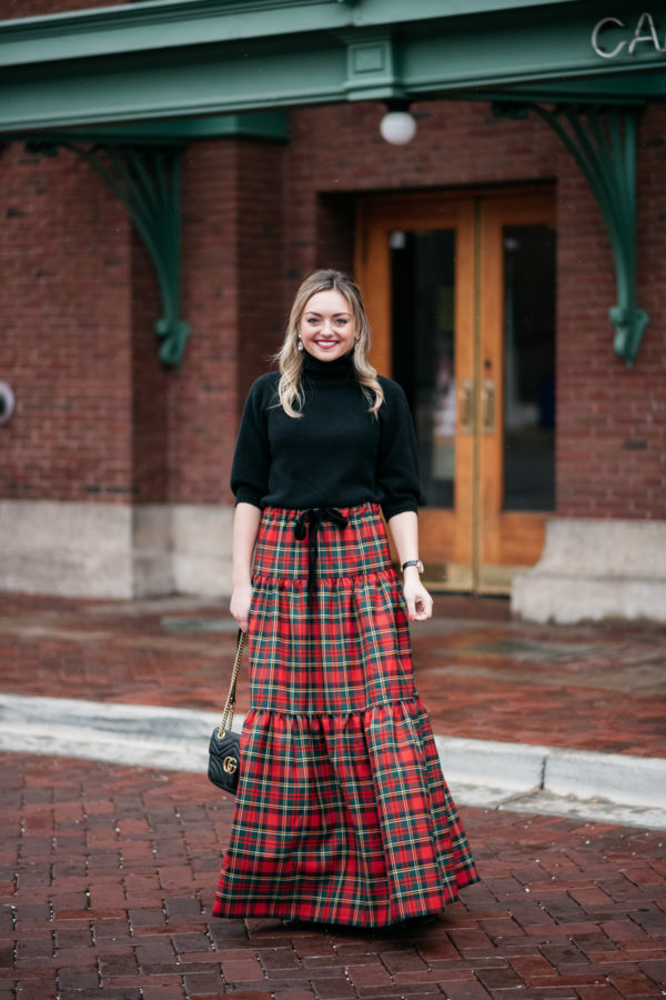 Jessica Sturdy wearing a black turtleneck and plaid tartan maxi skirt for the holidays.