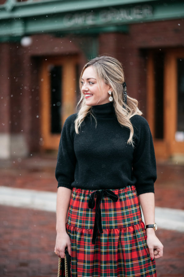 Jessica Sturdy wearing a black turtleneck sweater with sparkly Loren Hope crystal earrings and a J.Crew tartan plaid skirt with a velvet bow tie waist.