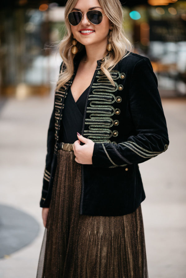 Chicago lifestyle blogger Jessica Sturdy wearing Ray-Ban aviators, a velvet band jacket with gold embroidery, a J.Crew bodysuit, and metallic gold pleated midi skirt with Kenneth Jay Lane gold earrings.