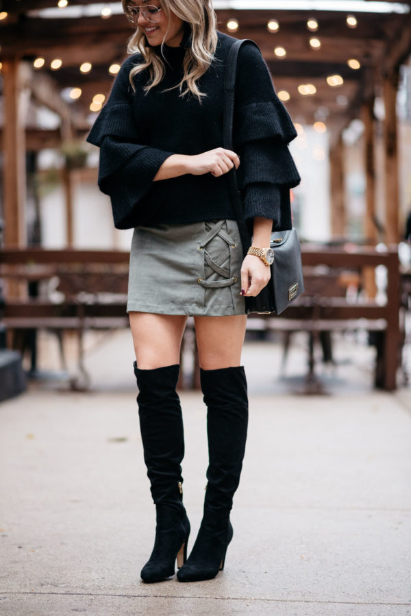 Jessica Sturdy of Bows & Sequins wearing an Endless Rose black ruffle sleeve sweater, Kensie suede lace-up skirt, and black OTK boots.
