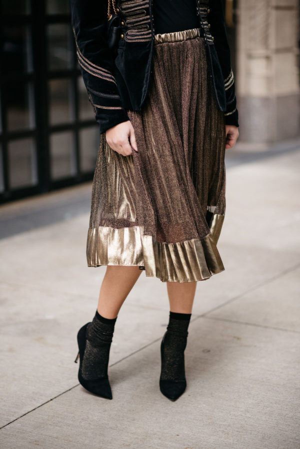 Jessica Sturdy wearing a metallic gold pleated midi skirt and Swildens black and gold shimmer socks with Kate Spade black suede Licorice pumps.