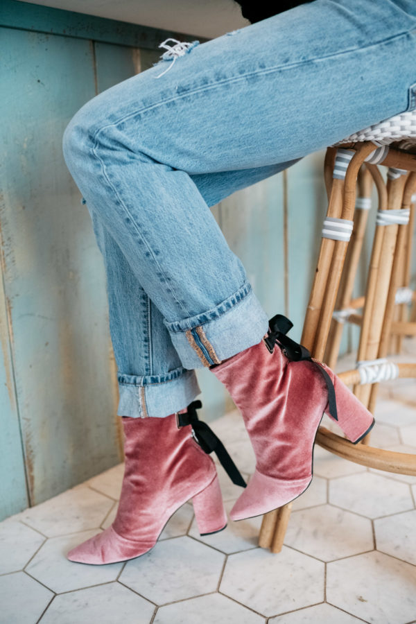 Fashion blogger Jessica Sturdy wearing pink velvet booties with a black bow and cuffed Levi's 501.