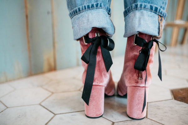 Fashion blogger Jessica Sturdy wearing pink velvet booties with a black bow and cuffed jeans.