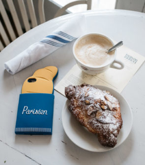 Blogger Jessica Sturdy with a French croissant phone case at the Maison Marcel cafe in Chicago.