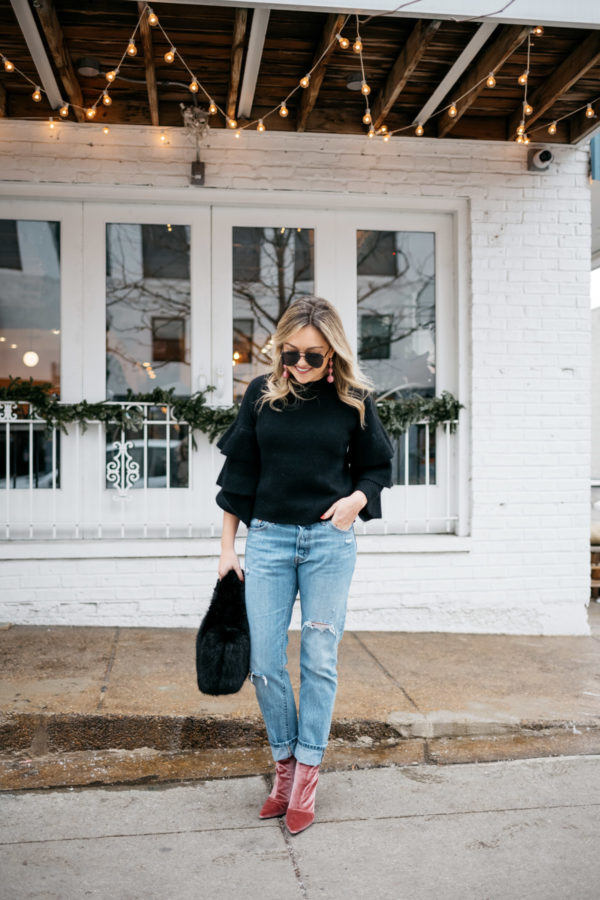 Jessica Sturdy wearing a black ruffle sweater, Levi's 501 boyfriend jeans, aviators, and pink velvet booties with a black fur bag.