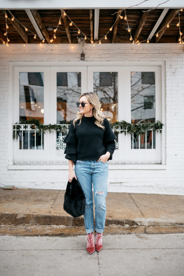 Jessica Sturdy wearing a black ruffle sleeve sweater, Levi's 501 boyfriend jeans, aviators, and pink velvet booties with a black fur bag.