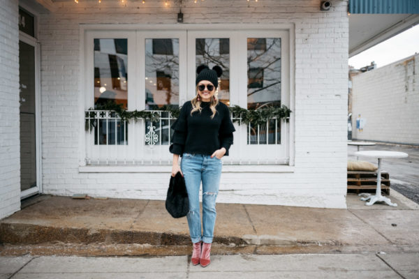 Jessica Rose Sturdy wearing a black ruffle sleeve sweater, Levi's 501 boyfriend jeans, aviators, and pink velvet booties with a black fur bag and pom pom beanie.