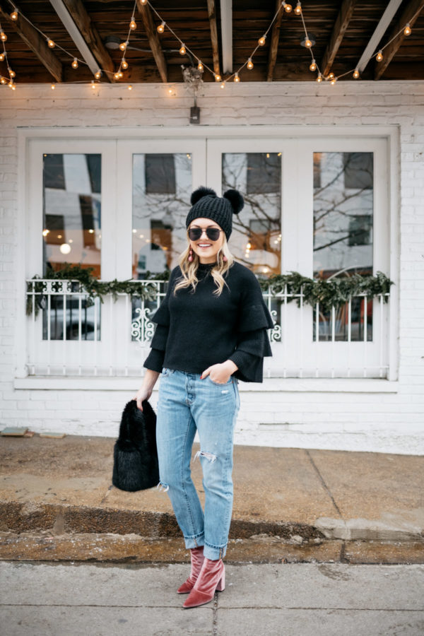 Lifestyle blogger Jessica Rose Sturdy wearing a black ruffle sleeve sweater, pink drop earrings, Levi's 501 boyfriend jeans, aviators, and pink velvet booties with a black fur bag and pom pom beanie at Maison Marcel in Chicago.