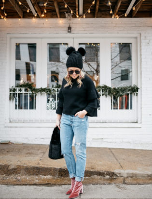 Lifestyle blogger Jessica Rose Sturdy wearing a black ruffle sleeve sweater, Levi's 501 boyfriend jeans, aviators, and pink velvet booties with a black fur bag and pom pom beanie.