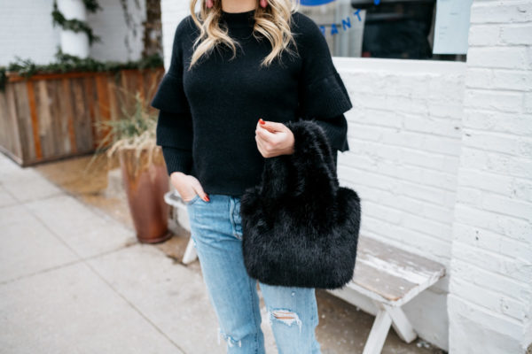 Fashion and lifestyle blogger Jessica Sturdy wearing a black ruffle sleeve sweater with boyfriend jeans and a black fur bag at Maison Marcel in Chicago.
