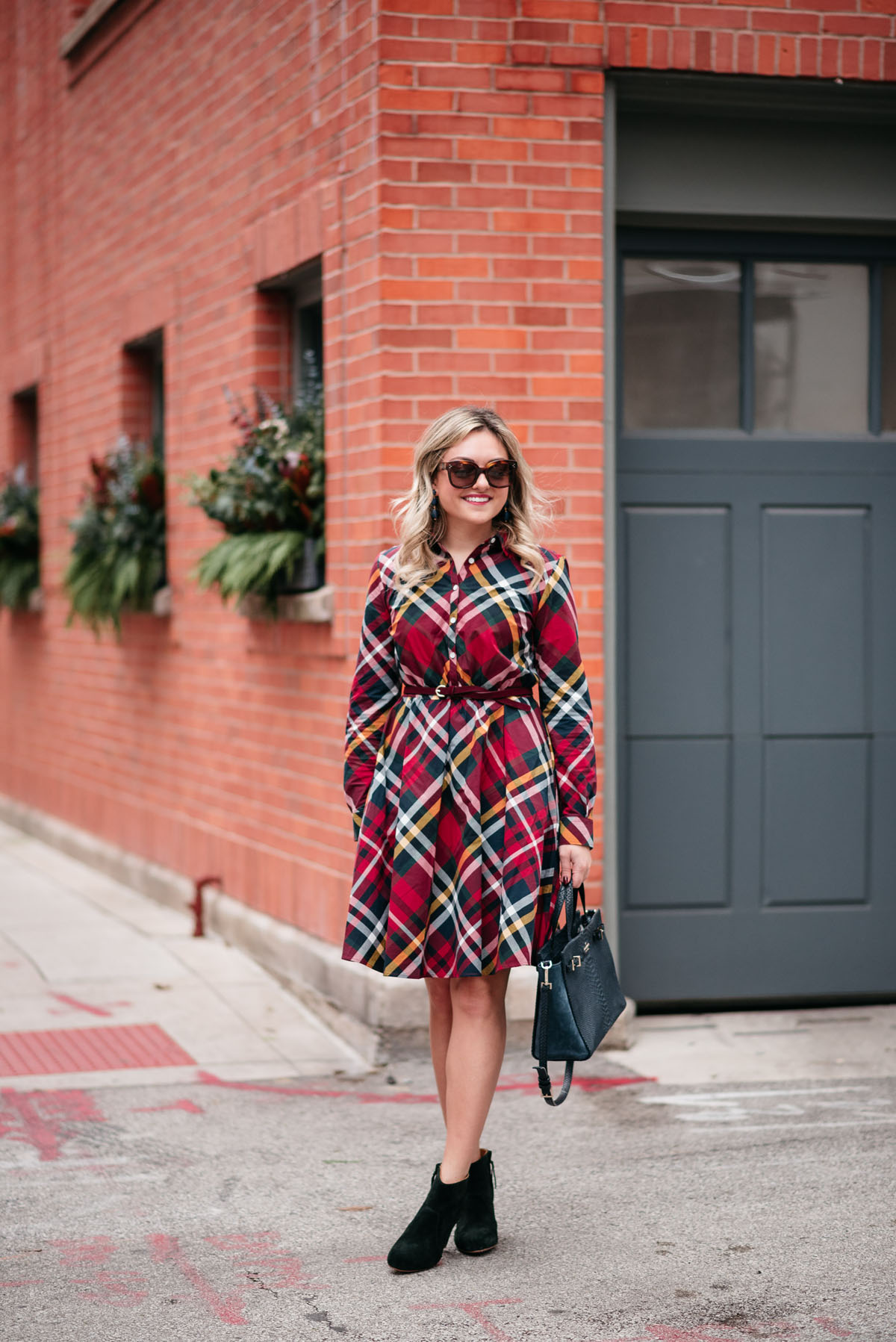 Jessica Rose Sturdy wearing tortoise sunglasses, a Brooks Brothers plaid dress, and booties with statement earrings and a navy Kate Spade tote.