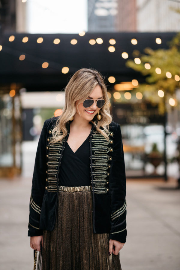 Blogger Jessica Rose Sturdy wearing Ray-Ban aviators, a velvet band jacket with gold embroidery, a J.Crew bodysuit, and metallic gold pleated midi skirt with Kenneth Jay Lane gold earrings.