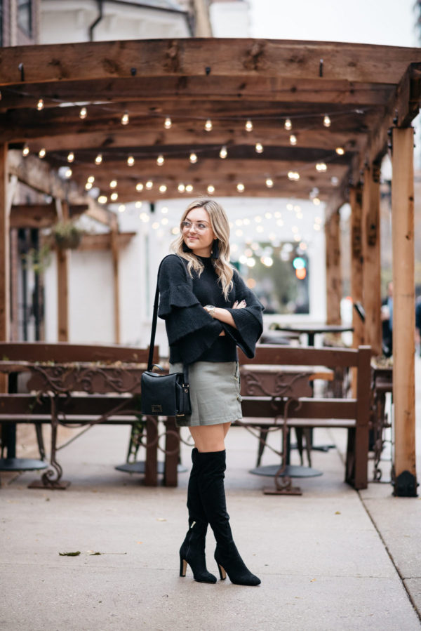 Jessica Sturdy wearing a black Endless Rose ruffle sleeve sweater, a suede lace-up skirt, black over the knee boots, and H&M clear glasses with a Lancel crossbody bag and Michael Kors watch.