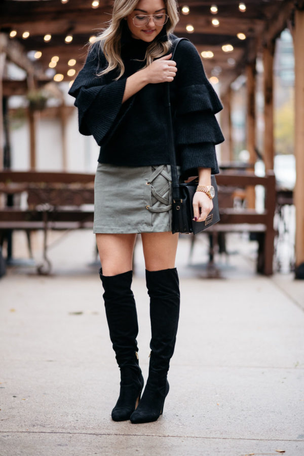 Jessica Sturdy of Bows & Sequins wearing an Endless Rose black ruffle sleeve sweater, Kensie suede lace-up skirt, and black OTK boots with a Michael Kors watch and a Lancel crossbody bag.