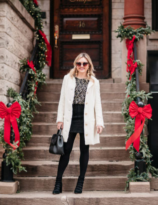Jessica Sturdy styling a white winter coat with a black and gold outfit for the holidays.