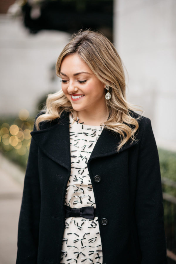 Chicago blogger Jessica Sturdy wearing Loren Hope drop earrings, a Sail to Sable bow dress, and a Ralph Lauren wool coat.