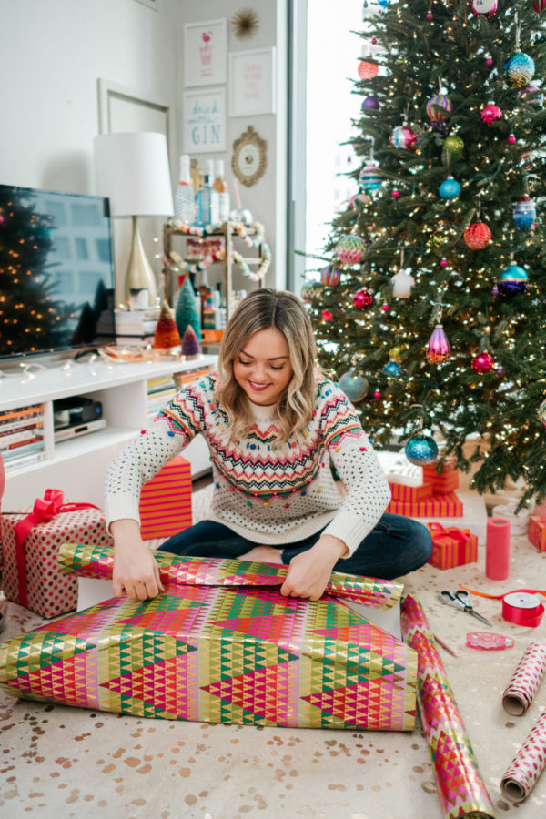 Jessica Sturdy wrapping Christmas presents with a colorful Christmas tree.