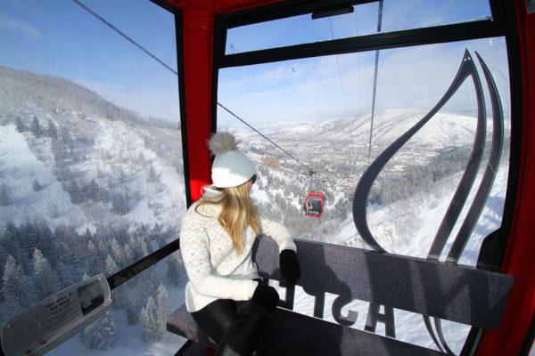 Jessica Sturdy on the Aspen Mountain Gondola wearing a fur pom beanie and cozy winter sweater.