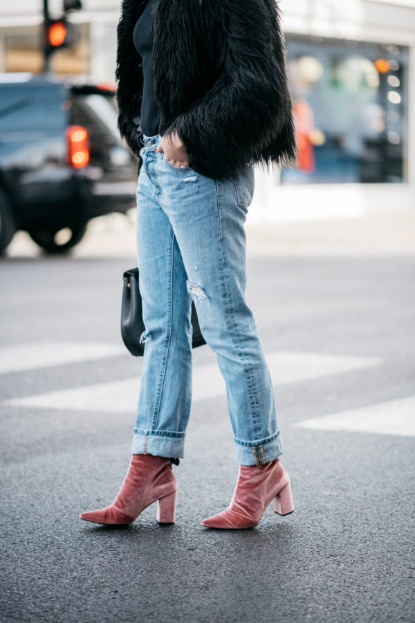 Jessica Sturdy of Bows & Sequins wearing a 1.State black faux fur coat, Old Navy black ribbed sweater, Levi's 501 boyfriend jeans, and Robert Clergerie pink velvet booties with a Polene Paris top-handle bag.
