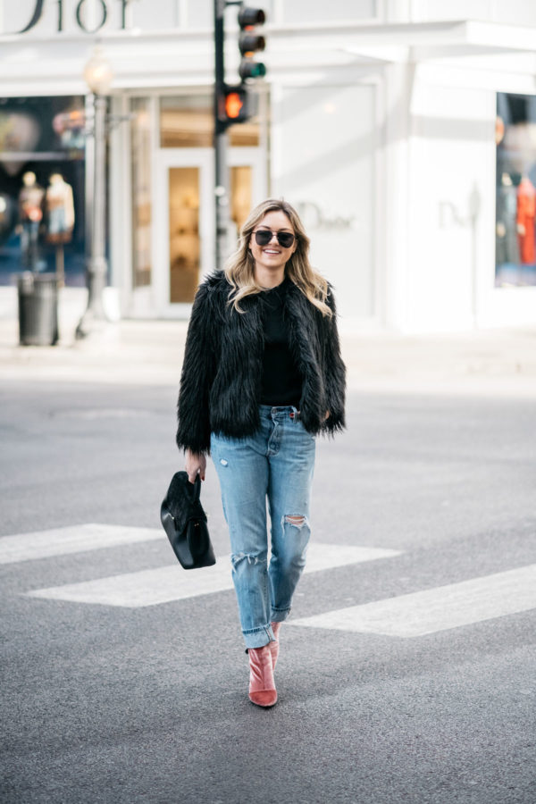 Jessica Sturdy sharing her winter uniform: black faux fur coat, Old Navy ribbed sweater, Levi's 501 boyfriend jeans, Robert Clergerie pink velvet booties, Polene Paris top handle bag, and Le Specs matte black aviators.