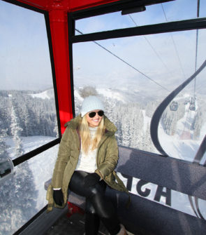 Jessica Sturdy wearing a green puffer coat and Sorel snow boots in the Apsen Mountain gondola.