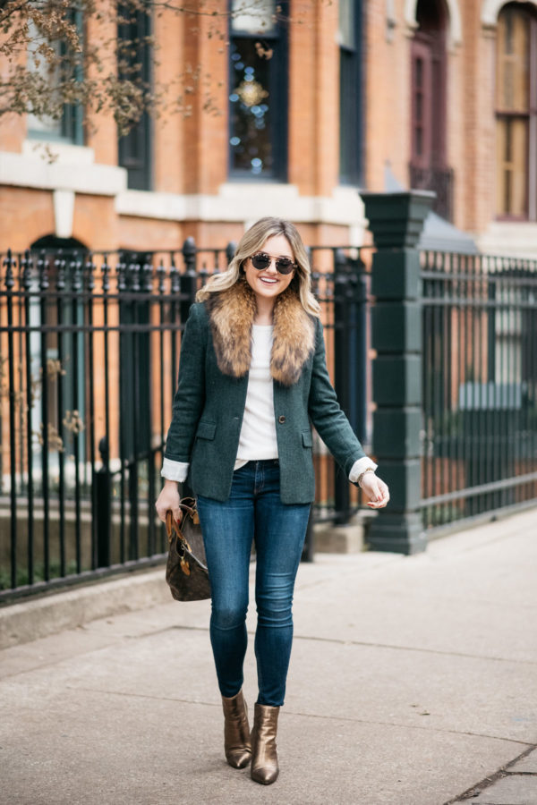 Jessica Sturdy wearing a green J.Crew blazer, an Old Navy ribbed tee, a fur collar from Paris, Rag & Bone skinny jeans, and Vince Camuto bronze booties with a Louis Vuitton monogrammed handbag, Illesteva Milan tortoise sunglasses, and a Michael Kors watch.