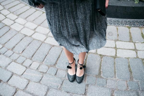 Jessica Sturdy wearing Kate Spade glitter pom-pom ankle strap heels with a silver dress.