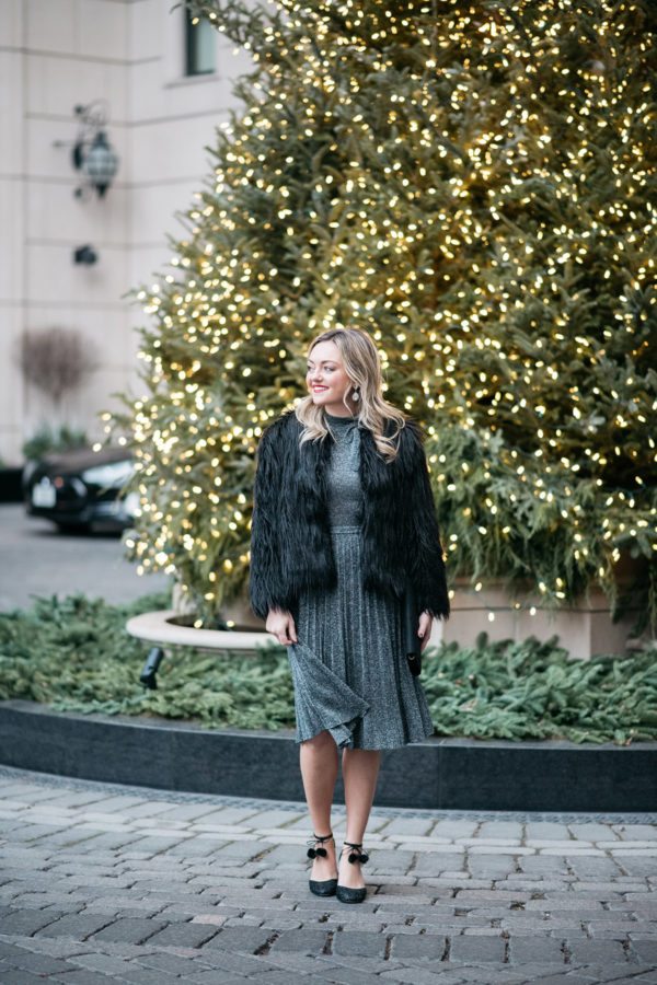 Jessica Sturdy wearing a silver dress in front of the Christmas tree at the Waldorf Astoria in Chicago.