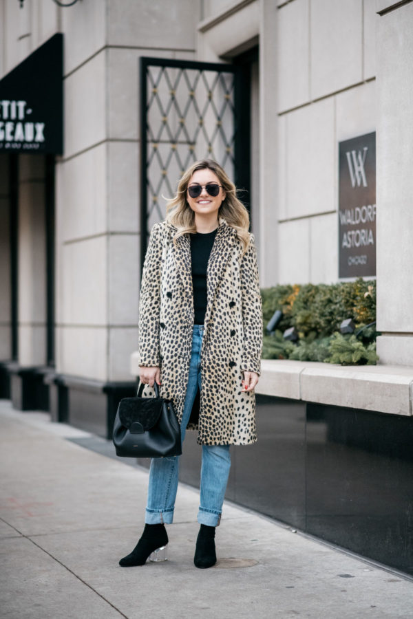 Jessica Sturdy wearing Le Specs matte black Prince aviators, Bows & Sequins leopard coat, Old Navy black ribbed sweater, Levi's 501 boyfriend jeans, and Steve Madden lucite booties with a Polene Paris black top-handle bag.