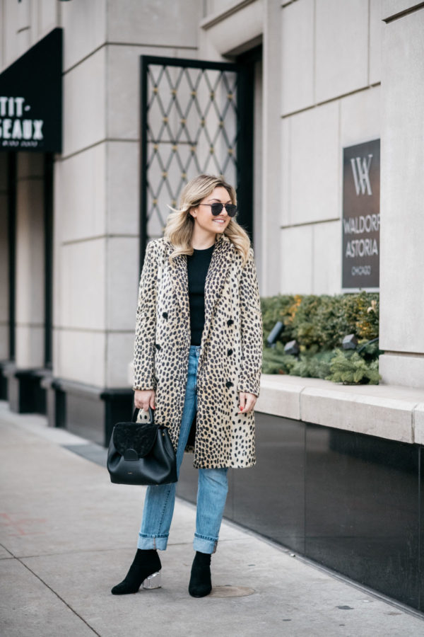 Chicago blogger Jessica Sturdy wearing Le Specs matte black Prince aviators, Bows & Sequins leopard coat, Old Navy black ribbed sweater, Levi's 501 boyfriend jeans, and Steve Madden lucite booties with a Polene Paris black top-handle bag.