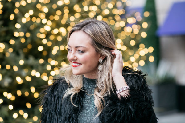 Jessica Sturdy wearing sparkly earrings, a silver dress, and a black fur coat.