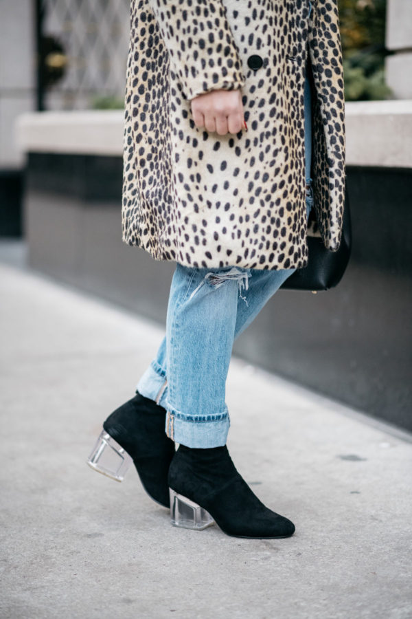 Jessica Sturdy wearing Le Specs matte black Prince aviators, Bows & Sequins leopard coat, Levi's 501 boyfriend jeans, and Steve Madden lucite booties with a Polene Paris black top-handle bag.