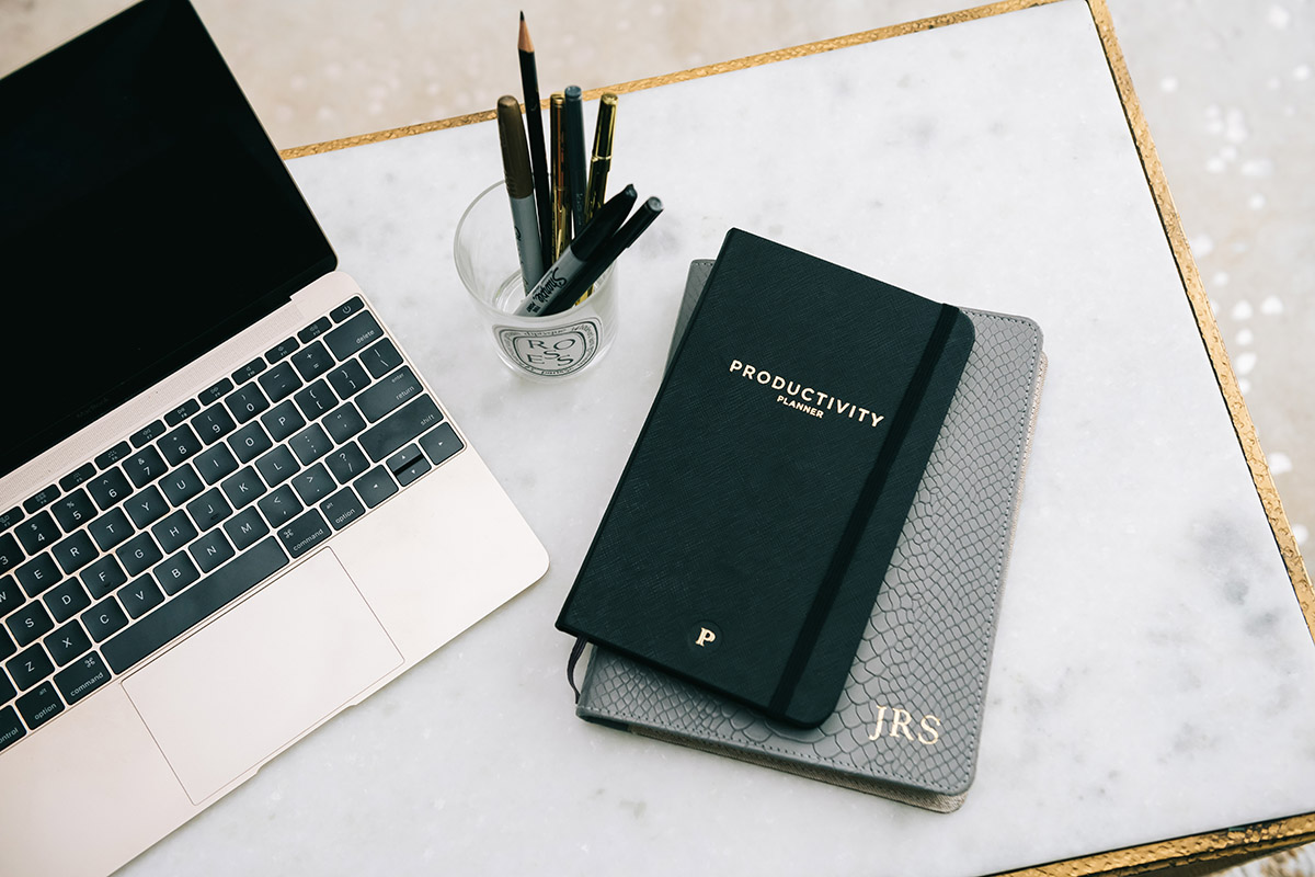 A gold MacBook laptop on a marble table with a Diptyque jar of markers, pens, and pencils, alongside a Productivity Planner and a monogrammed leather Journal.