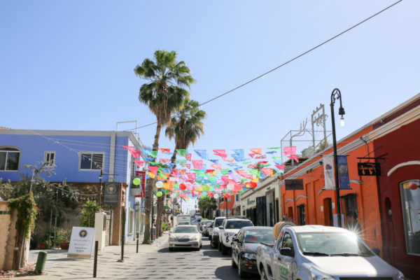 Jessica Sturdy shares photos from exploring San Jose del Cabo in Mexico. Colorful flags hanging between buildings.