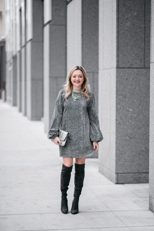 Bows & Sequins wearing a long sleeve silver dress with over the knee boots.