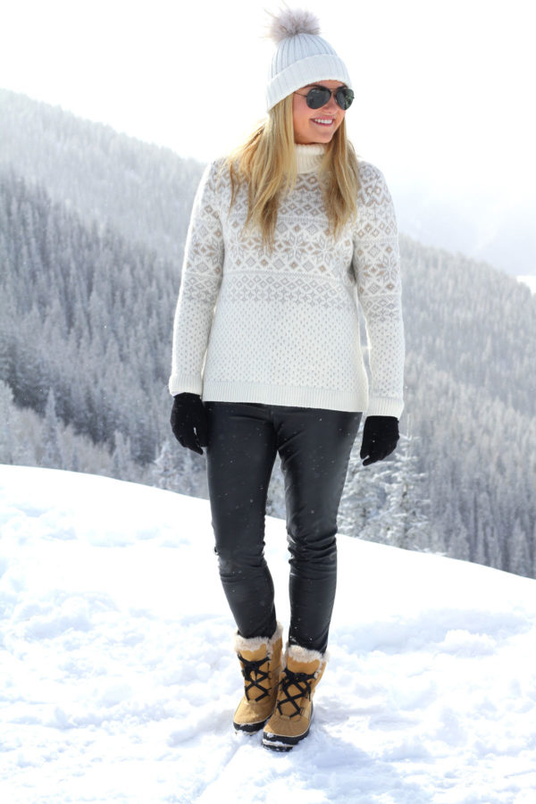 Jessica Sturdy wearing a fairisle turtleneck, leather pants, Sorel boots, gloves, and a beanie in the snow in Aspen.