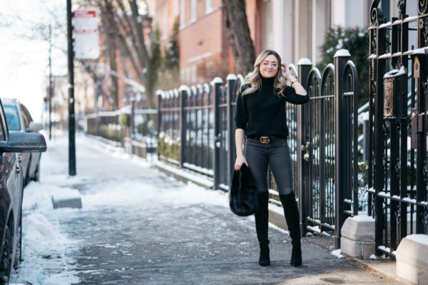 Jessica Rose Sturdy wearing a black Max Mara turtleneck, a gold Gucci GG logo belt, Rag & Bone skinny jeans, and over the knee boots with H&M clear glasses and a J.Crew shearling bag.