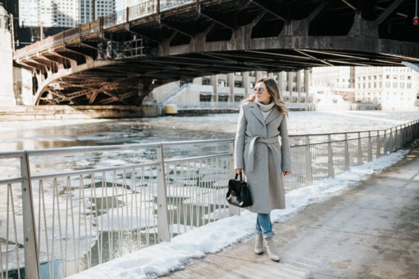 Chicago lifestyle blogger Jessica Rose Sturdy wearing a Claudie Pierlot grey wool coat, grey cashmere sweater, boyfriend jeans, and grey suede booties with mirrored sunglasses and a Polene top handle bag.