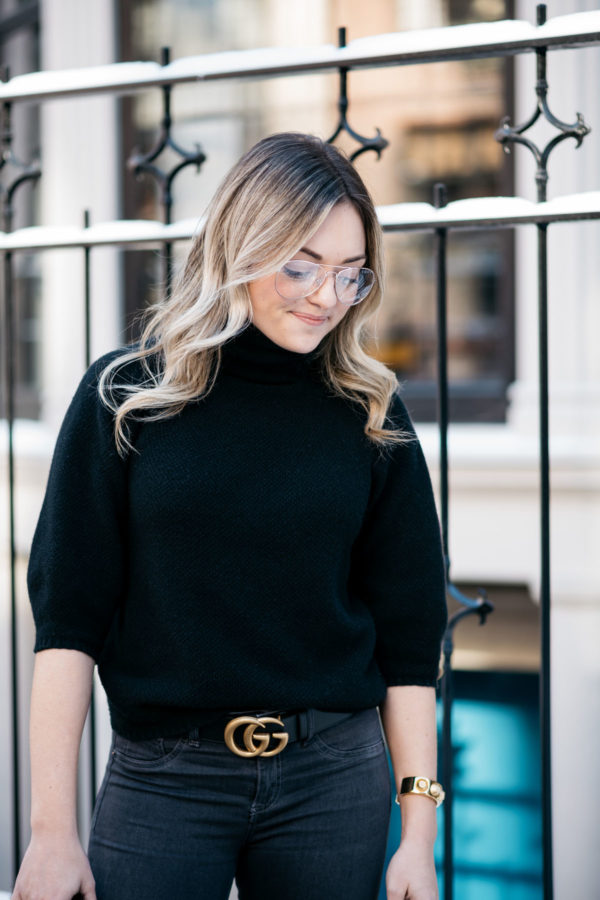 Jessica Sturdy, a Chicago fashion and travel blogger, wearing H&M clear glasses, a Max Mara black turtleneck, and a Gucci GG gold logo belt.
