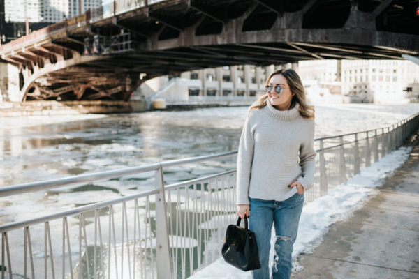 Jessica Sturdy wearing a Vineyard Vines cashmere sweater with Rag & Bone boyfriend jeans, a Polene Paris satchel, and mirrored sunglasses.