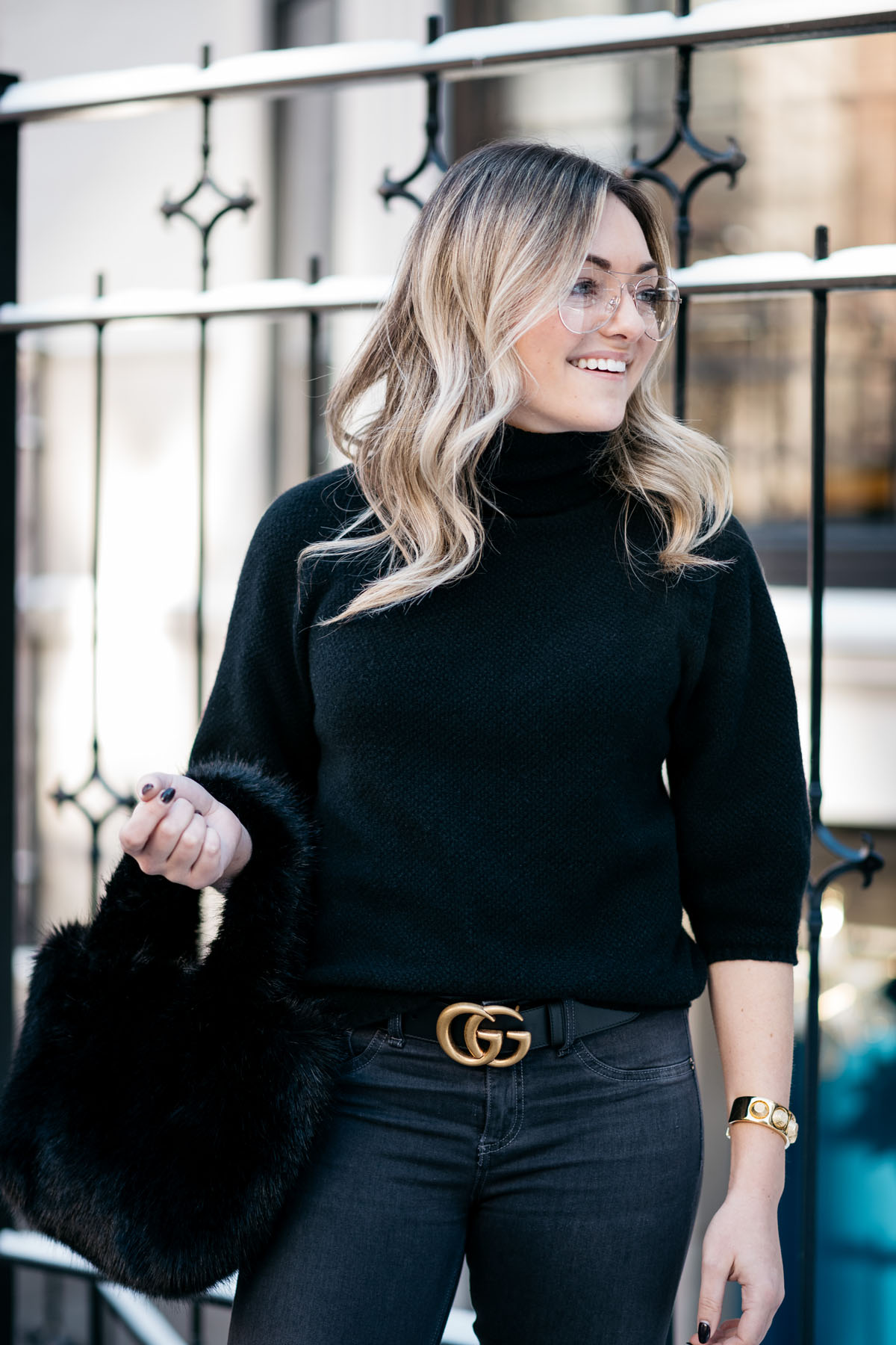 Jessica Sturdy, a Chicago fashion and travel blogger, wearing H&M clear glasses, a Max Mara black turtleneck, and a Gucci GG gold logo belt with a J.Crew shearling bag.