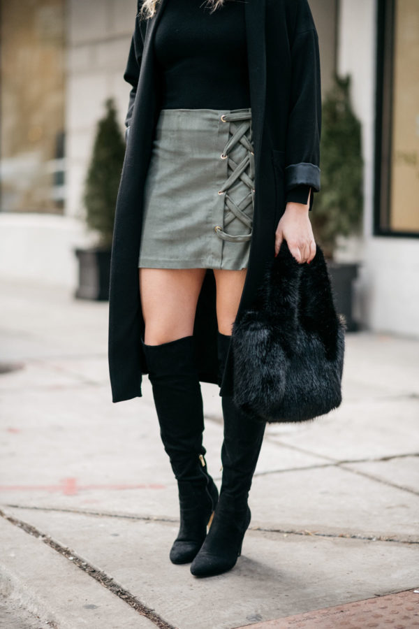 Chicago blogger Jessica Rose Sturdy wearing a long black coat with a Kensie olive green skirt, a J.Crew shearling handbag, and black over the knee boots.