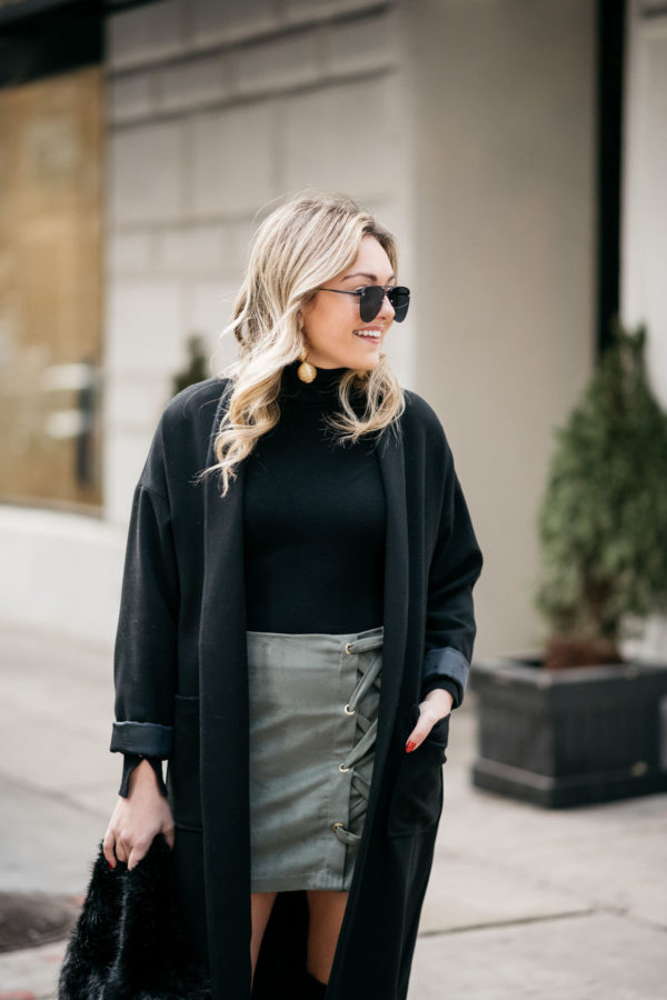 Chicago fashion blogger Jessica Sturdy wearing Le Specs matte black aviators, Kenneth Jay Lane earrings, Les Petites long black coat, Zara turtleneck, and Kensie olive green skirt with a J.Crew shearling handbag.