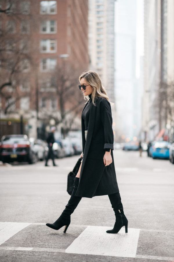Jessica Sturdy wearing a Les Petites long black crepe coat with a J.Crew shearling handbag, over the knee boots, and Le Specs matte black aviators.