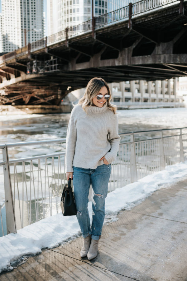 Jessica Sturdy wearing a grey Vineyard Vines cashmere sweater, Rag & Bone boyfriend jeans, mirrored sunglasses, and grey suede booties with a Polene Paris bag.