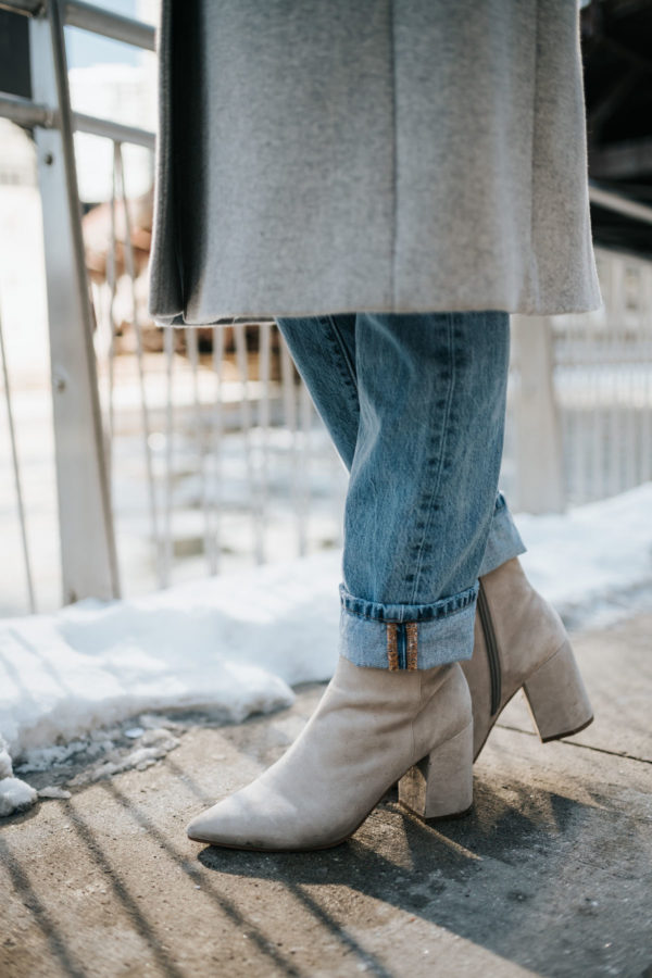 Jessica Sturdy wearing a grey coat, Rag & Bone boyfriend jeans, and Linea Paolo grey suede booties.