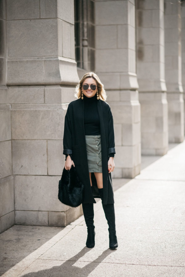 Jessica Sturdy wearing Le Specs matte black aviators, Kenneth Jay Lane earrings, a Zara turtleneck, Les Petites long crepe coat, Kensie olive green skirt, and black over the knee boots with a J.Crew shearling handbag.