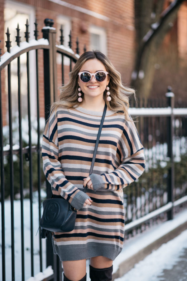 Chicago blogger Jessica Sturdy wearing a Tularosa pink and grey stripe sweater dress for winter with a navy blue Gucci bag, pink sunglasses, and Bauble Bar earrings.