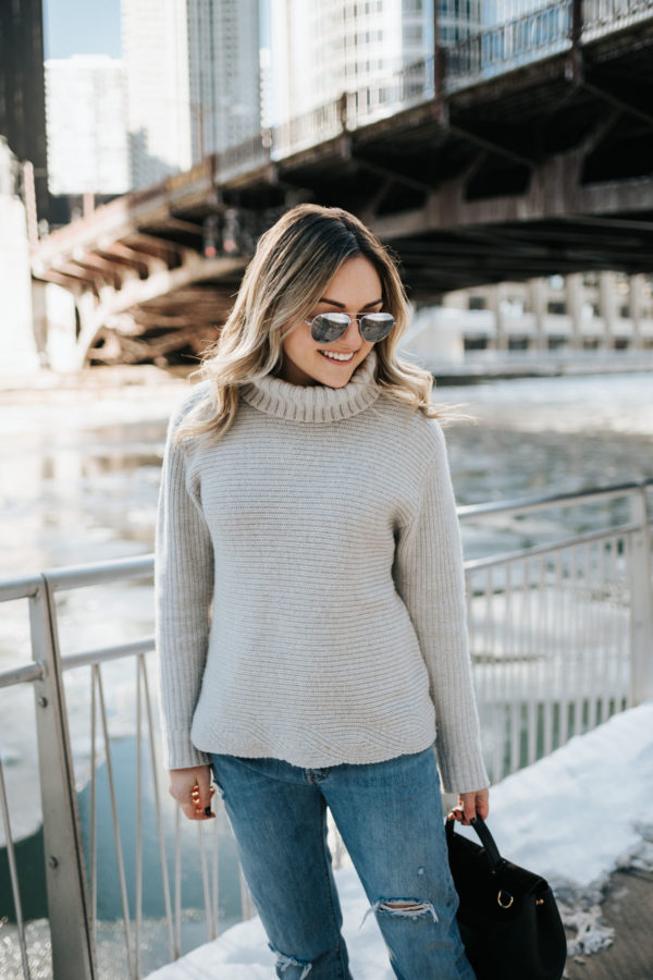 Jessica Sturdy wearing a grey Vineyard Vines cashmere turtleneck, Rag & Bone boyfriend jeans, and mirrored sunglasses with a Polene Paris bag.