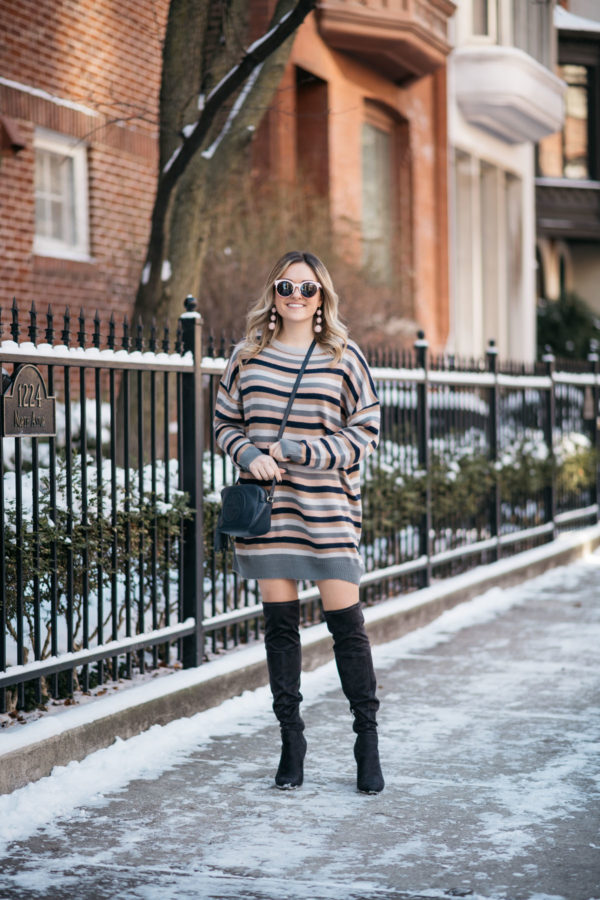 Chicago blogger Jessica Sturdy wearing a Tularosa stripe sweater dress for winter with over the knee boots, a navy blue Gucci bag, pink sunglasses, and Bauble Bar earrings.
